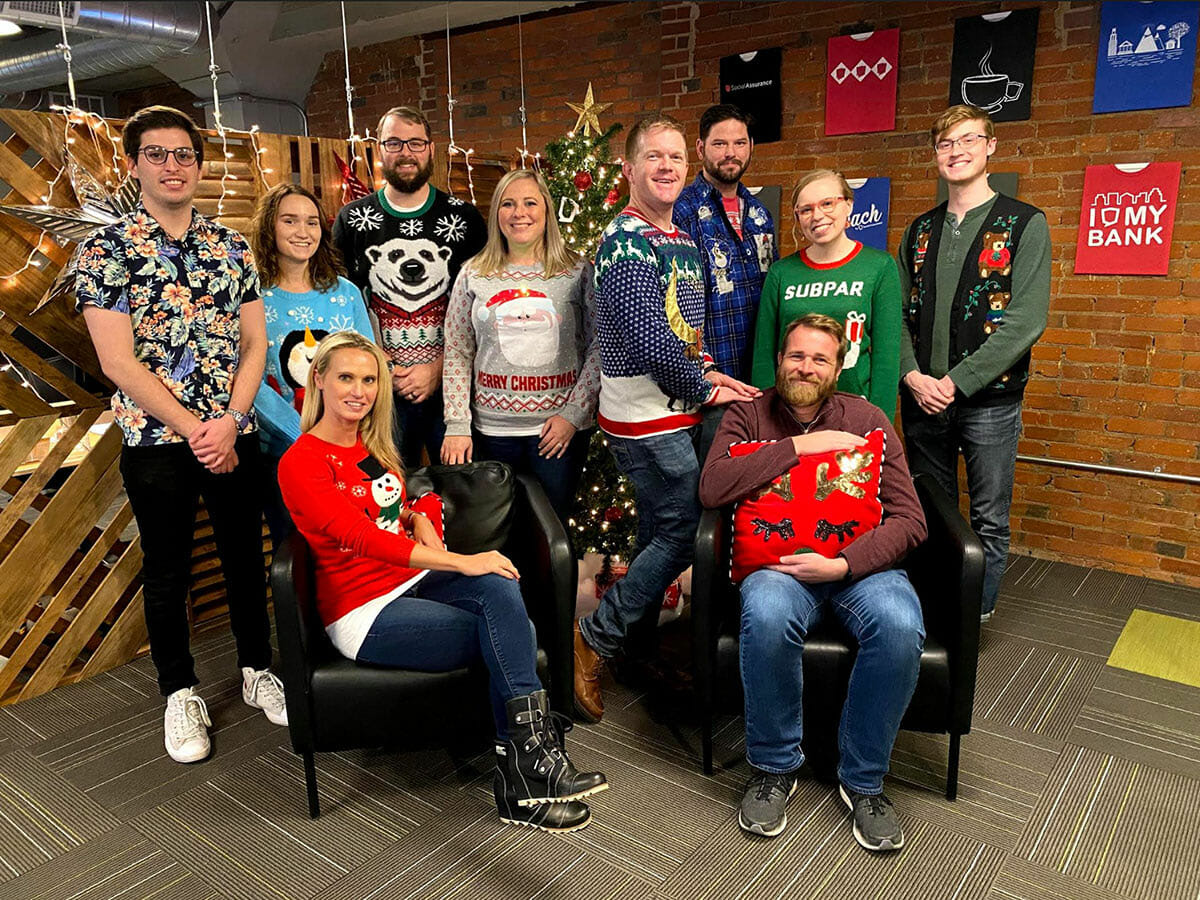 Group of Social Assurance employees standing close together in holiday sweaters
