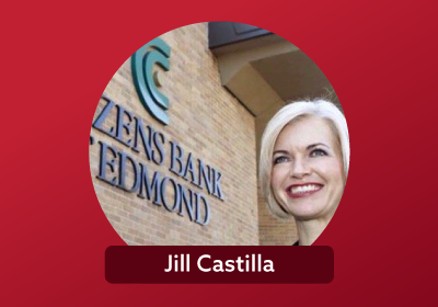 headshot of a smiling Jill Castilla, a female banker with short white hair