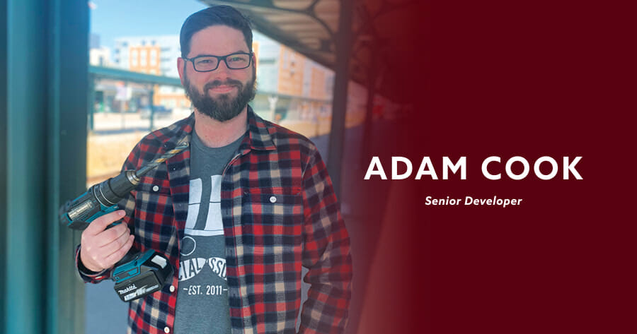 man holding a drill in a flanel shirt with the words adam cook, senior developer