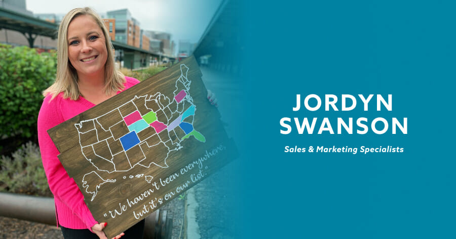 smiling woman holding wooden map of the united states with the words, jordyn swanson, sales and marketing specialist