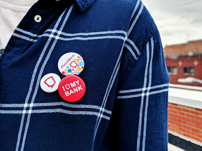 person wearing a dark blue flannel shirt with social assurance pins